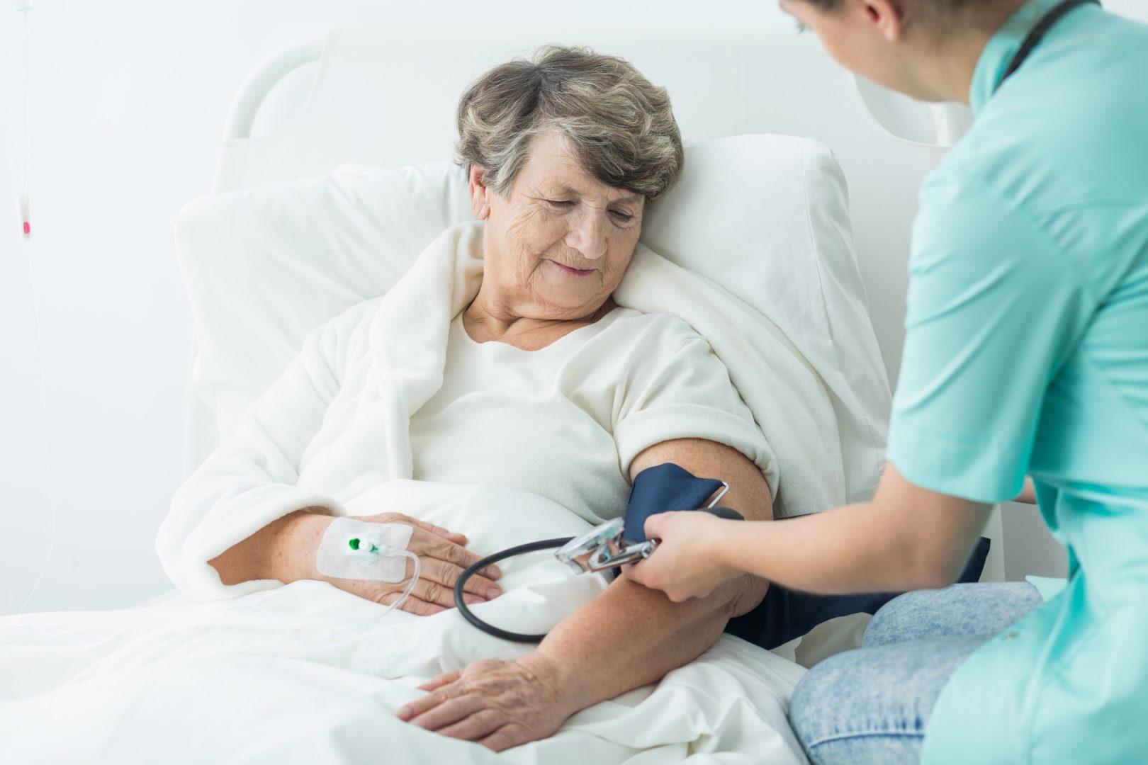 Vepleegster meet bloeddruk oudere vrouw