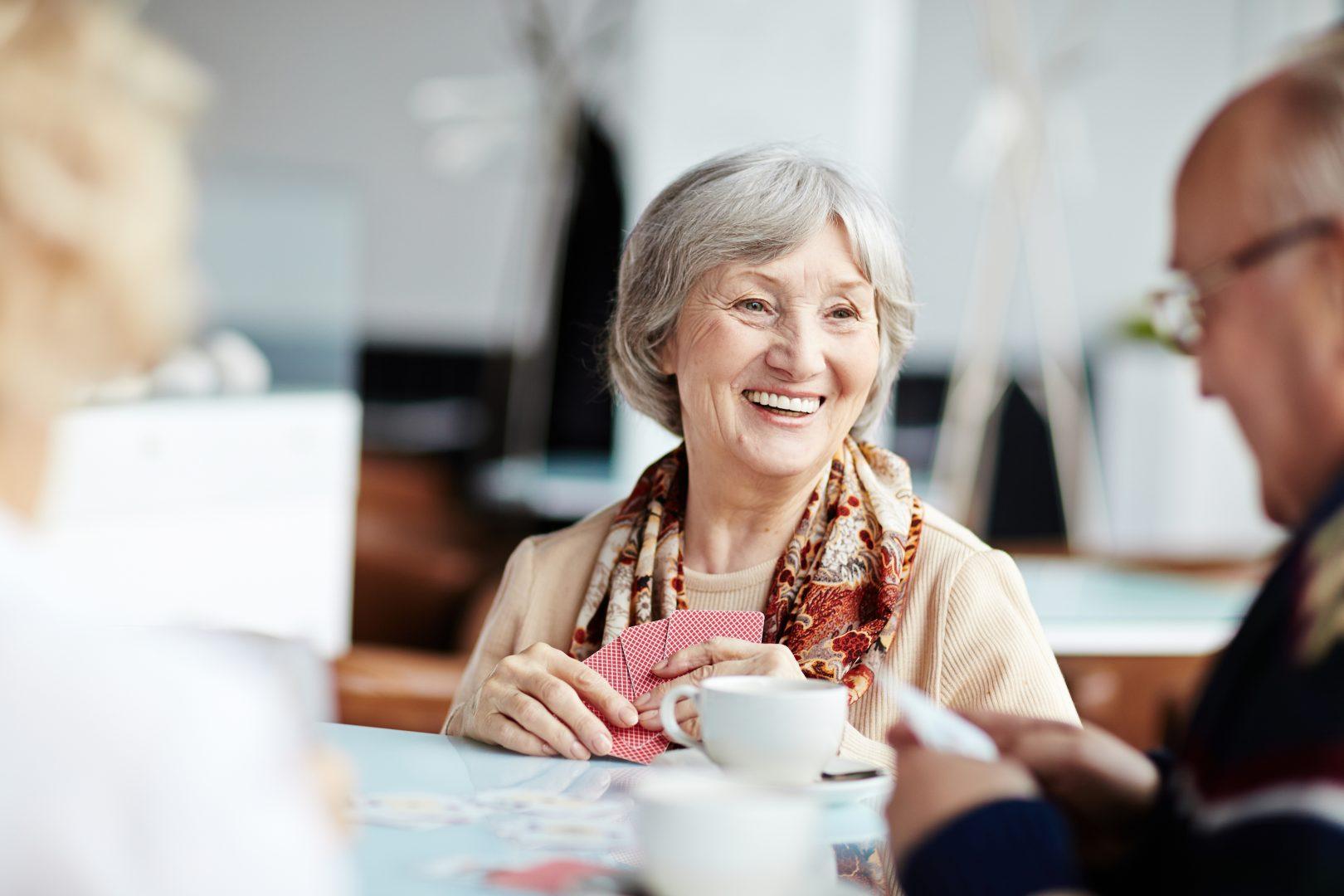 Oudere vrouw speelt al lachend kaartspel