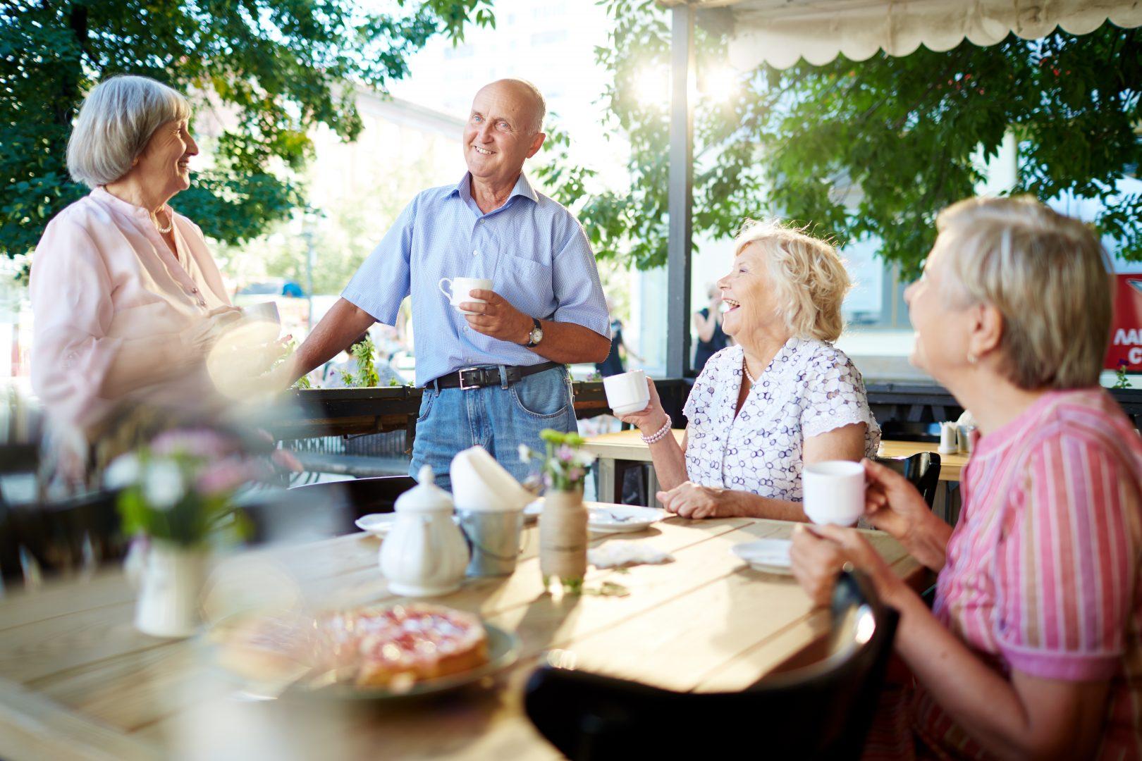 Ouderen drinken al lachend koffie op terras