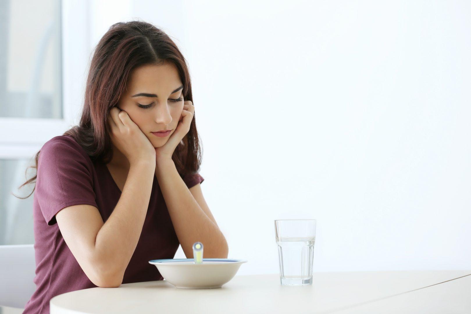 Jonge vrouw kijkt zonder eetlust naar kom voor zich