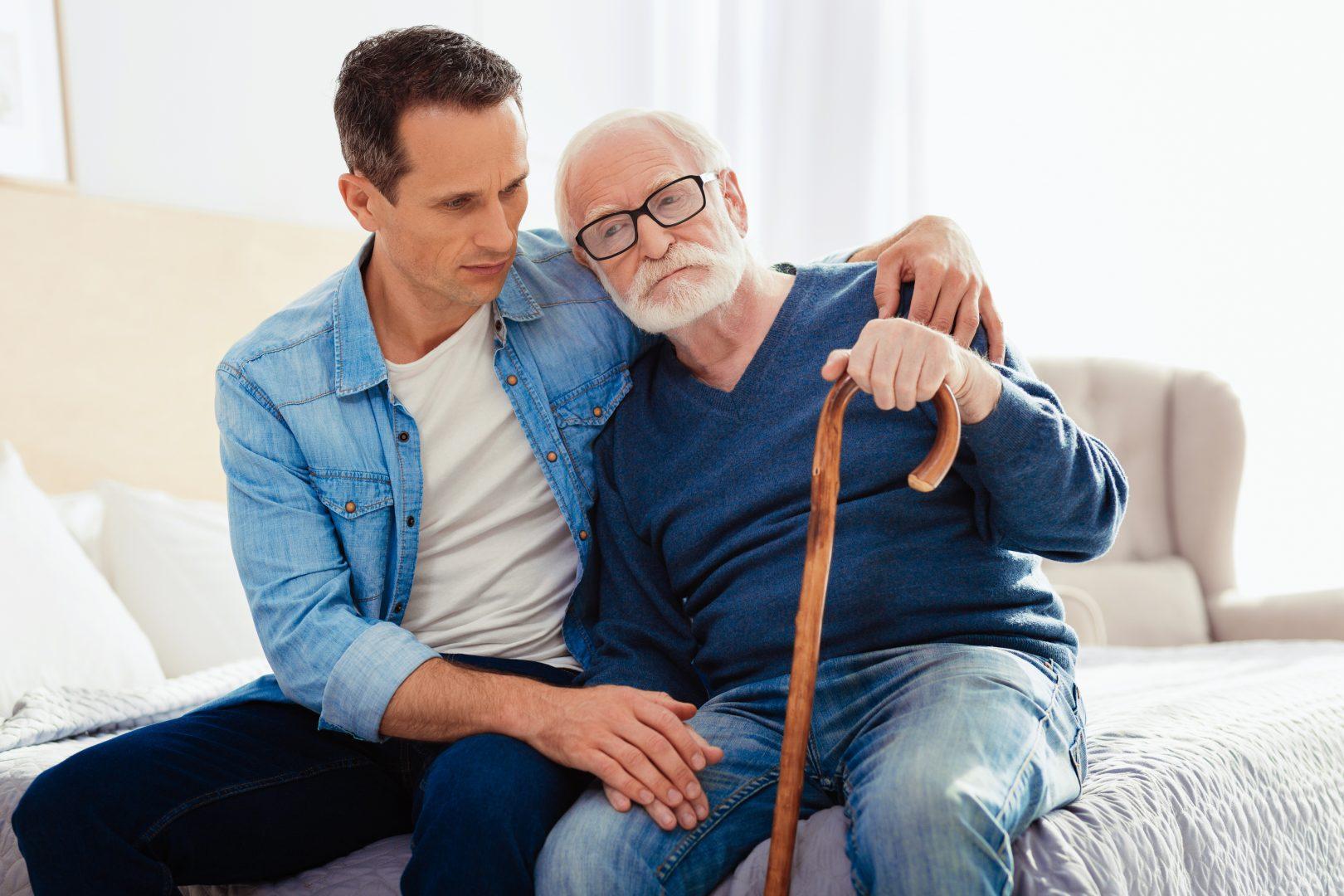 Jongere man zit bezorgd op bed met oude vader